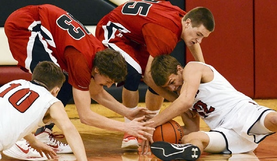 Sutton's Tanner Peterson battles with Sandy Creek's Trace Gordanier and Colton Shuck for this loose ball Thursday night. Peterson and the Mustangs would hold off the Cougars, winning the game, 54-50. Looking on for the Mustangs is Garrett Leach